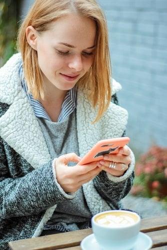 job étudiant : une jeune femme en train d'utiliser son smartphone