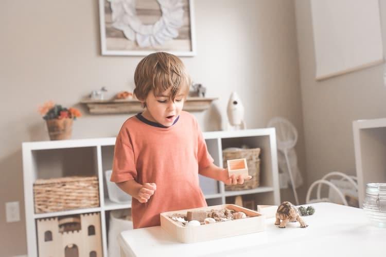 un petit garçon en train de faire des découvertes avec son bac sensoriel