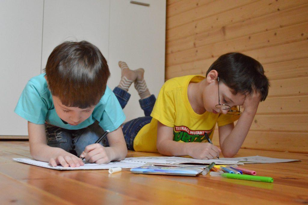 comment faire ses devoirs : deux enfants qui font leurs coloriages par terre