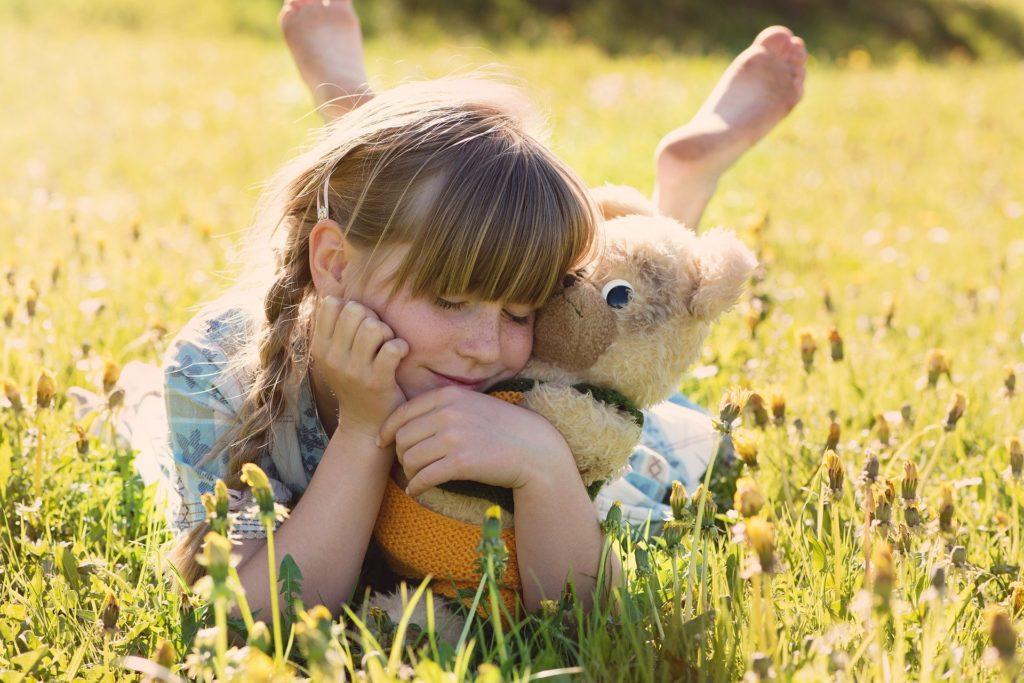 garde d'enfants périscolaire : une petite fille qui s'amuse avec sa peluche