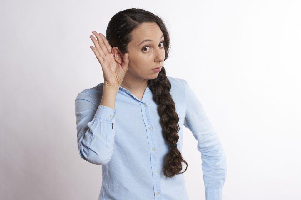 qualités babysitter : une jeune femme en train de prêter l'oreille pour mieux écouter