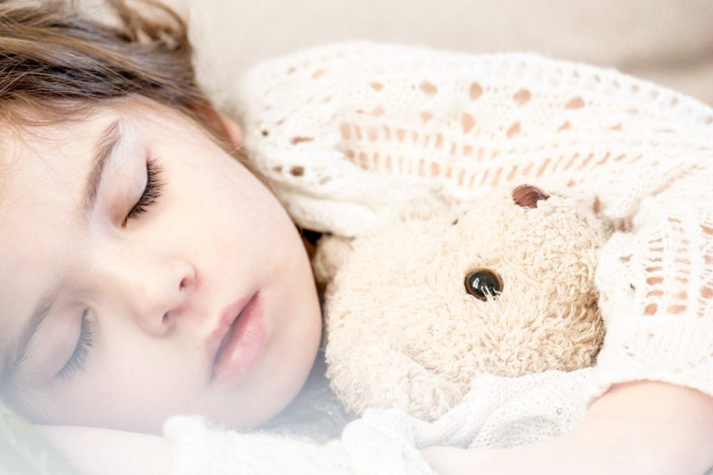une petite fille qui fait la sieste avec son doudou