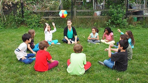un groupe d'enfant avec leur babysitter en train de jouer à passe the ball