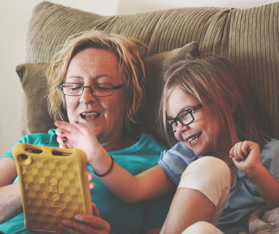 une maman qui s'amuse avec sa fille en utilisant une tablette digitale