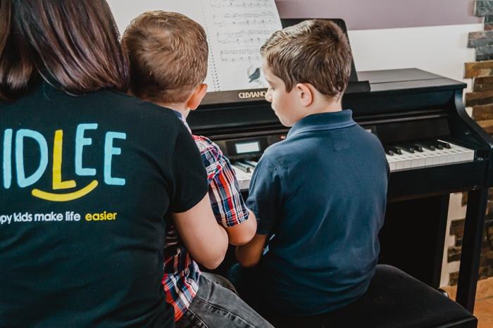Une nounou top Kidlee en train de faire du piano avec les deux petits garçons qu'elle garde