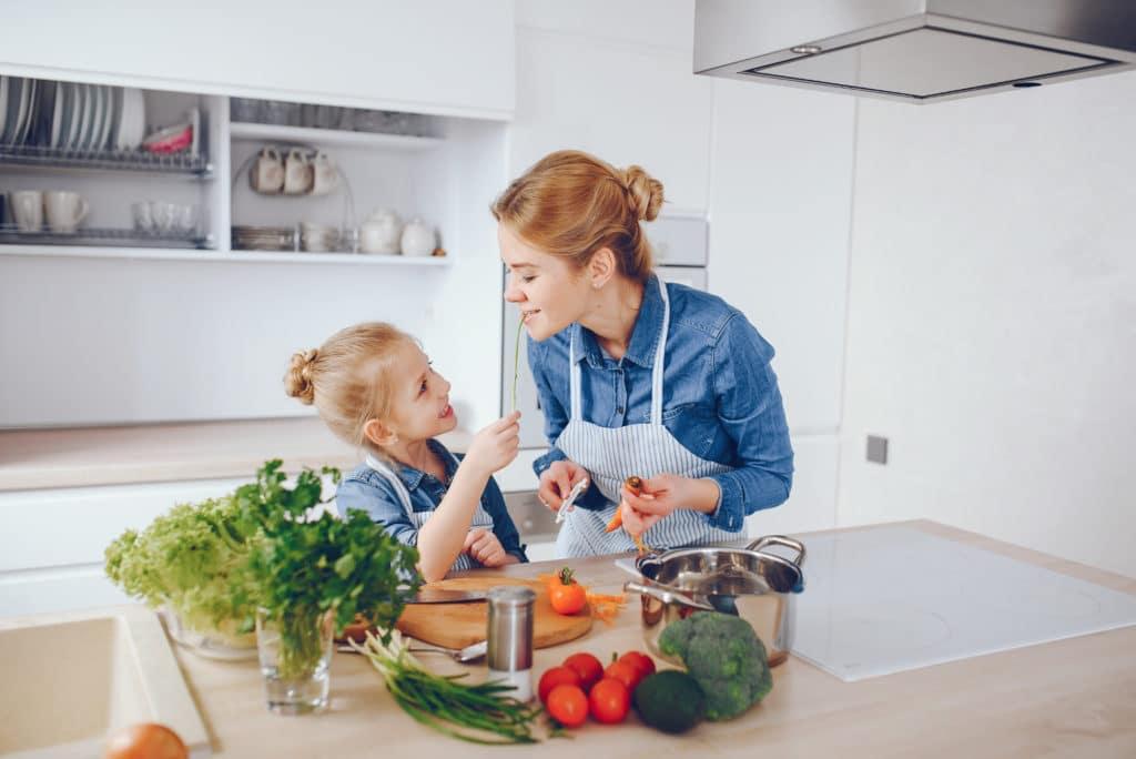 Enfant refuse de manger :  une petite fille qui cuisine avec sa babysitter