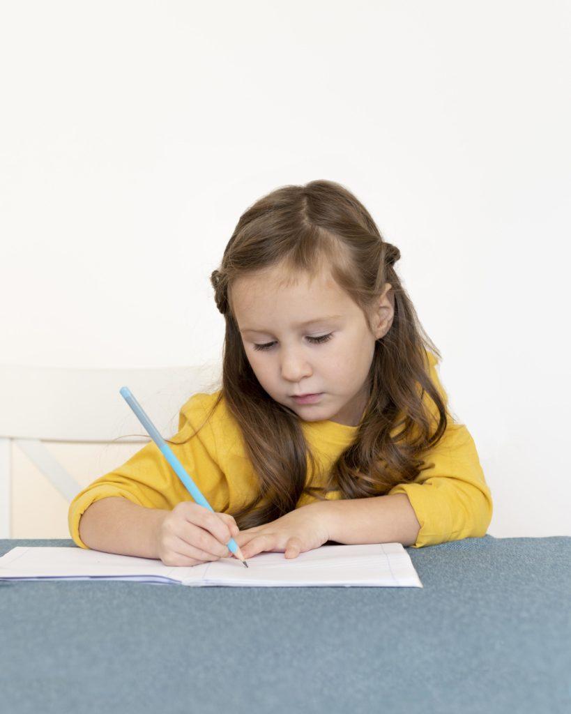 Aide aux devoirs : petite fille qui fait ses devoirs