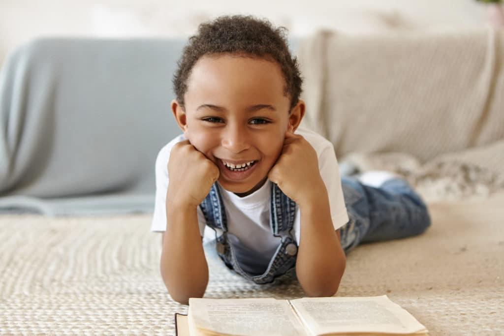 Aide aux devoirs : un enfant allongé sur le tapis et qui lit un livre avec le sourire