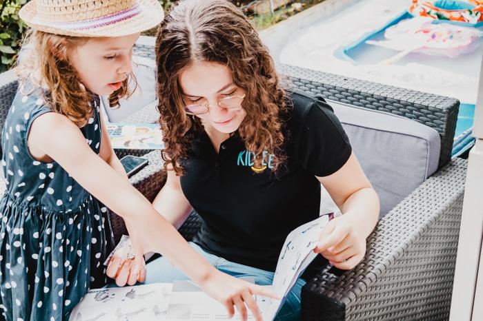 Agence baby sitting :  une babysitter Kidlee qui regarde un livre avec la petite fille qu'elle garde
