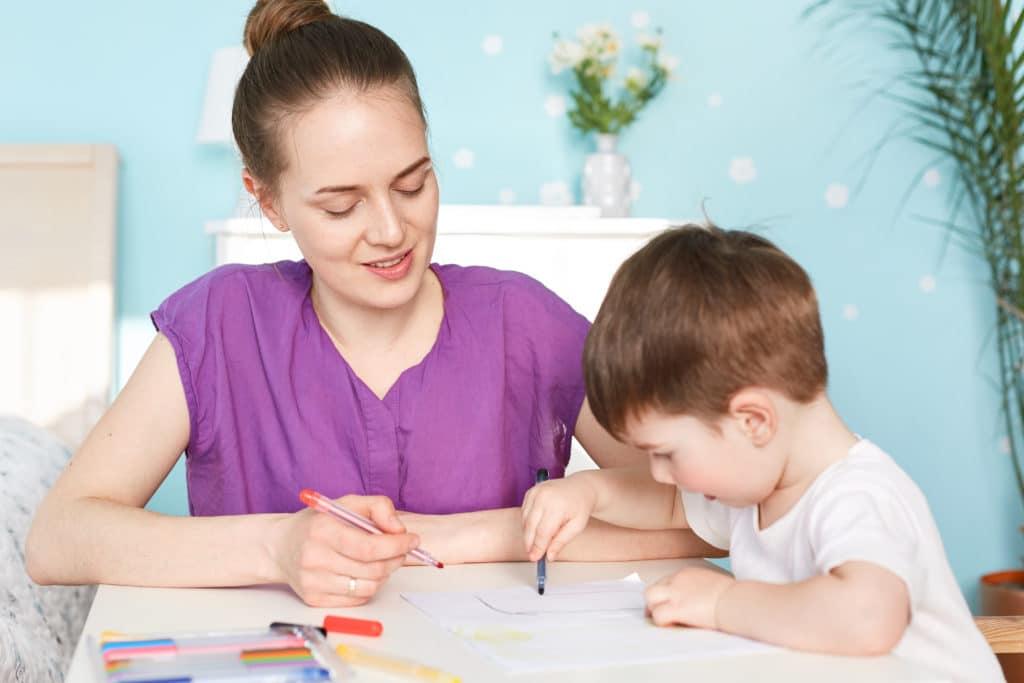 babysitter qui dessine avec un enfant