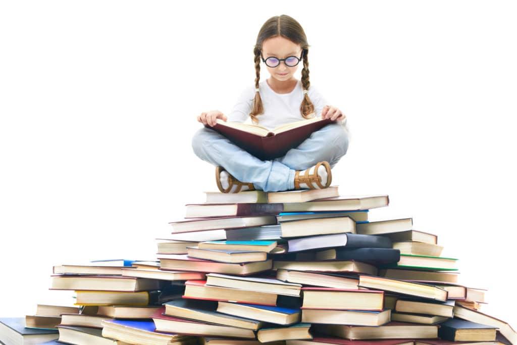 Portrait d'une petite fille avec un livre entre les mains et assise sur une montagne de livres