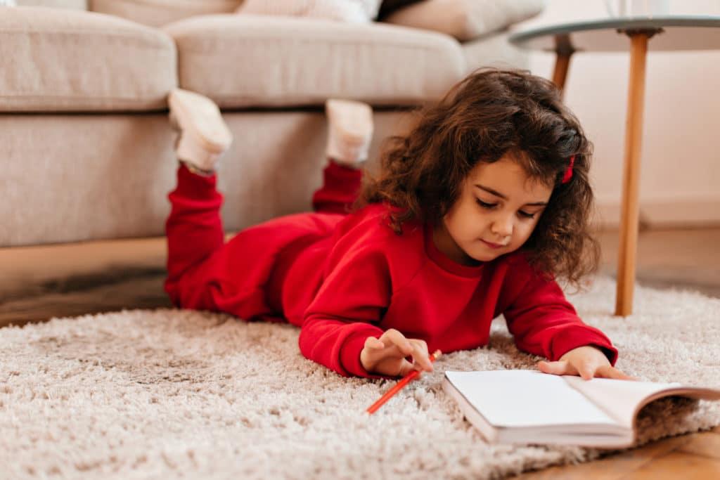 Petite fille allongé parre terre avec son crayon et son petit livre