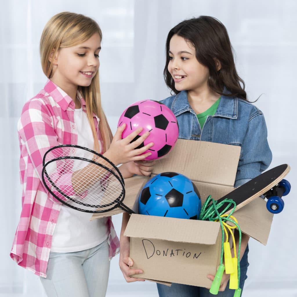 deux préado qui s'apprêtent à donner tout un carton de jouets