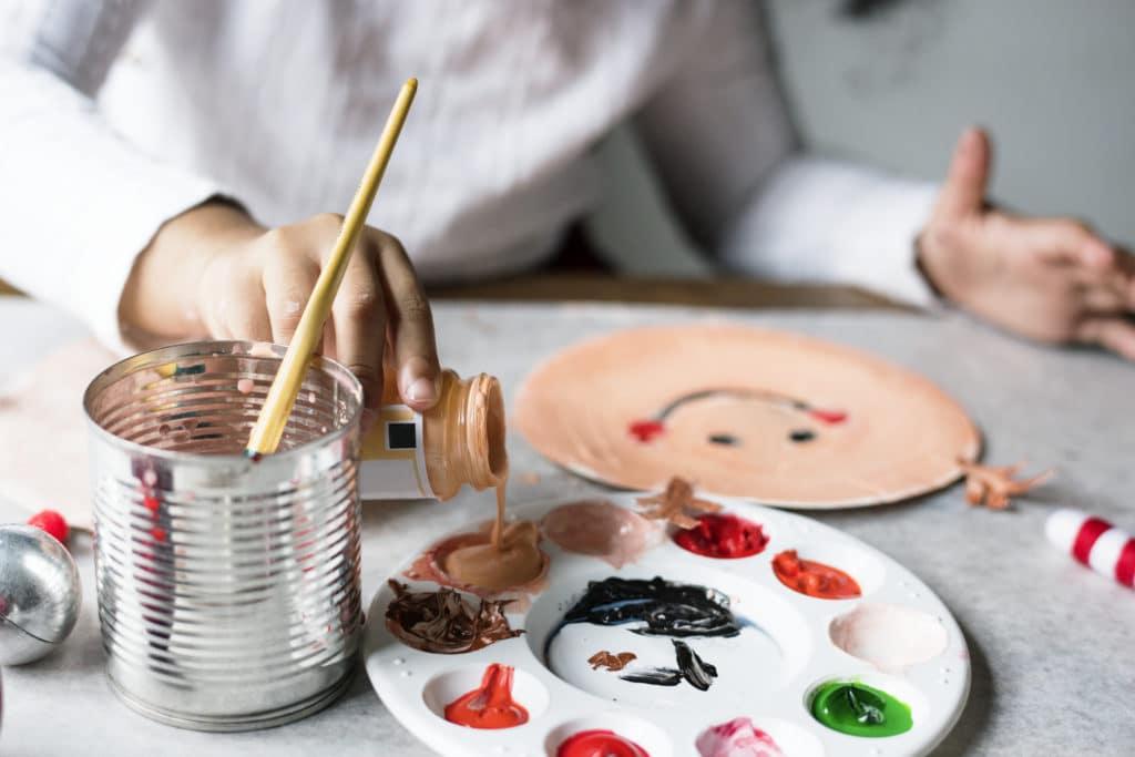 préparer son baby sitting :  enfant en train de peindre une assiette en papier