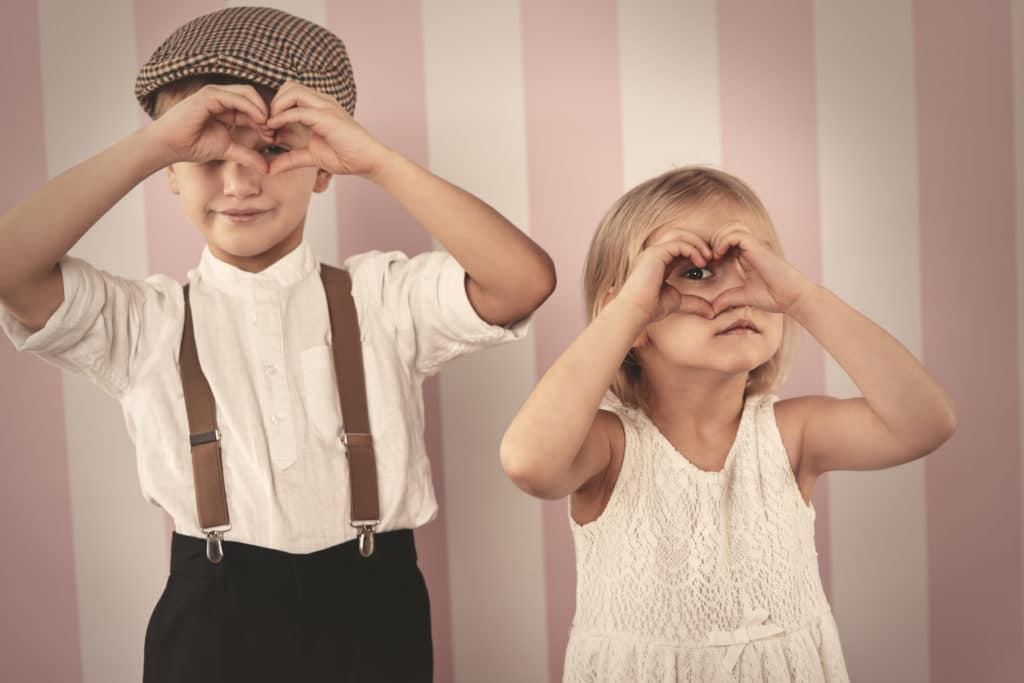 Une petite fille et un petit garçon en train de regarder à travers leurs doigts qui forment un coeur
