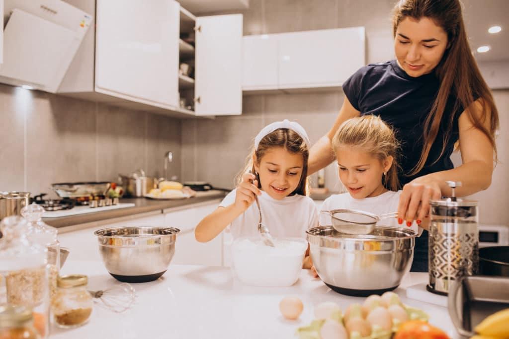 garde d'enfant à domicile :  une babysitter en train de cuisiner avec les enfants qu'elle garde