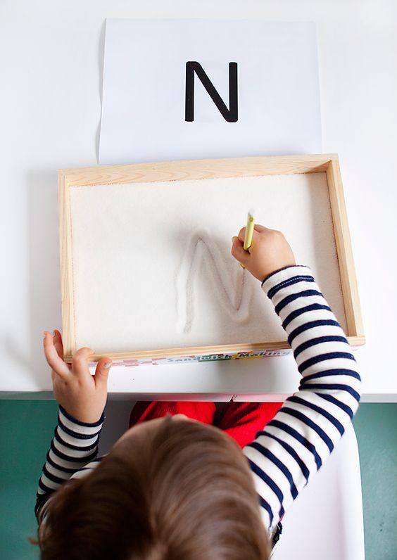Activités à faire avec les enfants : un enfant en train d'écrire le lettre N dans un bac à sable