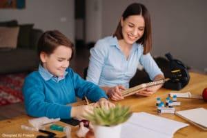 Babysitter étudiante en train d'aider l'enfant à faire ses devoirs