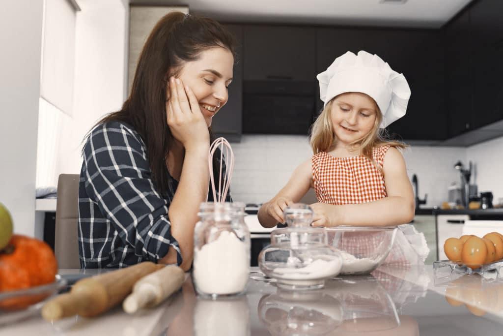 nounou bilingue :  une babysitter qui fait de la pâtisserie avec une petite fille