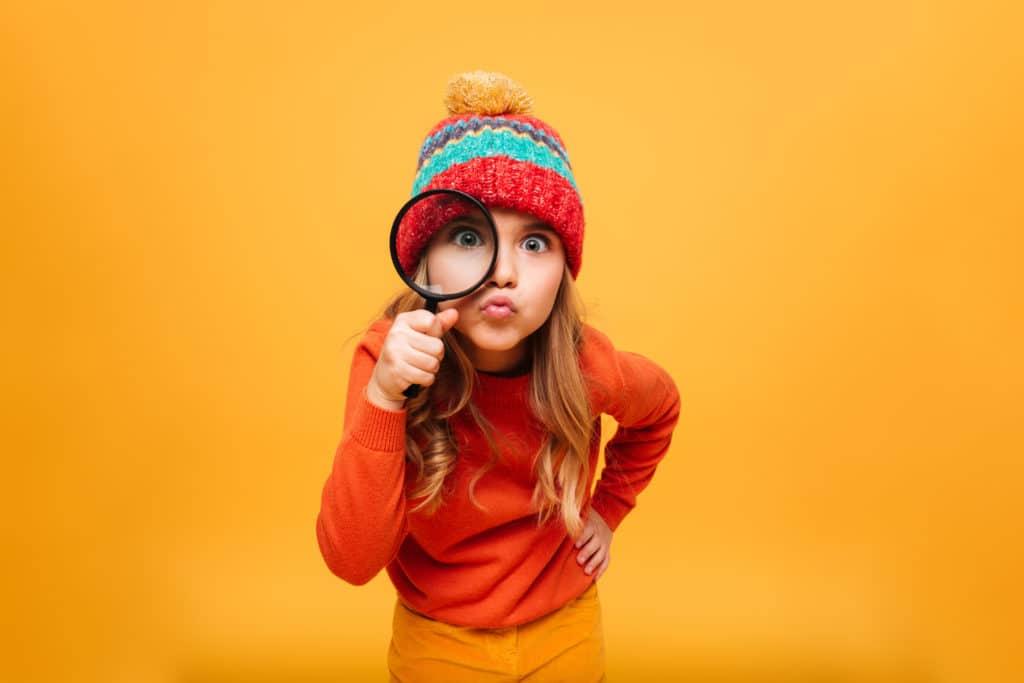 nounou bilingue :  une petite fille qui regarde à travers une loupe