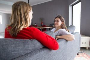 Garde d'enfants à domicile en train de discuter avec une maman