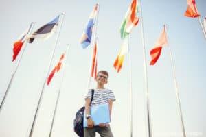 Trouver une nounou bilingue : un enfant debout autour des drapeaux