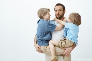 Garde d'enfants à domicile : Un papa qui tiens ses deux garçons dans les bras