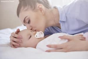 rituel du coucher : une maman qui embrasse son bébé