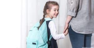Une baby sitter qui récupère un enfant à sa sortie d'école