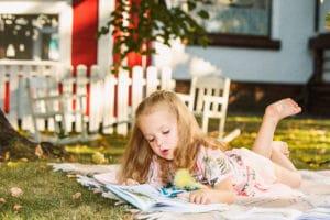 Une fille qui lit son cahier de vacances