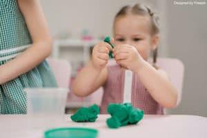 activités d'éveil : une fille en train de jouer avec la pâte à modeler