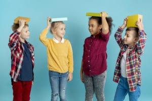 Des enfants avec un livre sur la tête
